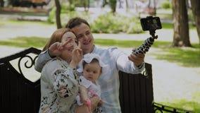 Szczęśliwa rodzina z dzieckiem bierze selfie na ławce w parku zdjęcie wideo