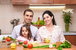 Szczęśliwa rodzina z dzieckiem w domowym kuchennym wnętrzu z świeżymi owoc i warzywo, kobieta w ciąży, zdrowy karmowy pojęcie Zdjęcia Stock