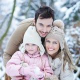 Szczęśliwa rodzina z dzieckiem w zimie zdjęcie royalty free