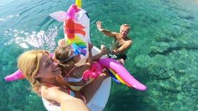 Szczęśliwa rodzina z dziewczyną bierze selfie w dennym miejsca siedzące na nadmuchiwanej jednorożec zbiory