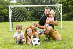 Szczęśliwa rodzina z futbolową piłką na polu zdjęcie royalty free
