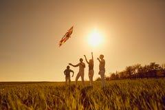 Szczęśliwa rodzina z kanią bawić się przy zmierzchem w polu obrazy royalty free