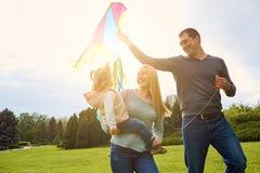 Szczęśliwa rodzina z kolorową kanią na naturze sunlight zdjęcia royalty free