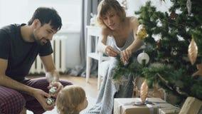 Szczęśliwa rodzina z małą córką dekoruje choinki w domu zbiory