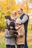 Szczęśliwa rodzina z pastylka komputerem osobistym w jesień parku Zdjęcie Stock