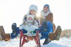 Szczęśliwa rodzina z saniem w zimie fotografia royalty free