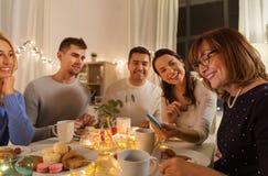 Szczęśliwa rodzina z smartphone przy herbacianym przyjęciem w domu zdjęcie stock