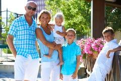 Szczęśliwa rodzina z trzy dziećmi stoi wpólnie Fotografia Stock