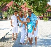 Szczęśliwa rodzina z trzy dziećmi stoi wpólnie Obrazy Stock
