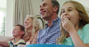 Szczęśliwa rodzinna dopatrywanie telewizja w żywym pokoju wpólnie zbiory