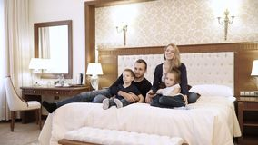 Szczęśliwa rodzinna dopatrywanie telewizja w pokoju hotelowego obsiadaniu na łóżku zdjęcie wideo