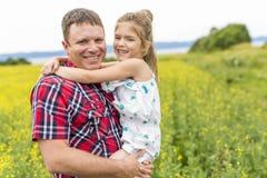Szczęśliwa rodzinna ojca i dziecka córka na kolorów żółtych kwiatach na naturze w lecie Zdjęcia Stock