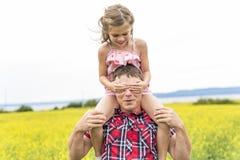 Szczęśliwa rodzinna ojca i dziecka córka na kolorów żółtych kwiatach na naturze w lecie Obrazy Royalty Free