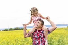 Szczęśliwa rodzinna ojca i dziecka córka na kolorów żółtych kwiatach na naturze w lecie Fotografia Royalty Free