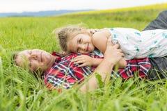 Szczęśliwa rodzinna ojca i dziecka córka na kolorów żółtych kwiatach na naturze w lecie Fotografia Stock