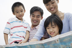 Szczęśliwa Rodzinna Patrzeje mapa Przeciw niebu Fotografia Stock