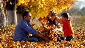 Szczęśliwa rodzinna radość i zabawa w naturze bawić się z jesień liśćmi, zwolnione tempo zbiory