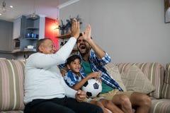Szczęśliwa rodzinna robi wysokość pięć podczas gdy oglądający mecz piłkarskiego Obrazy Royalty Free
