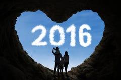 Szczęśliwa rodziny inside jama patrzeje liczby 2016 Obrazy Royalty Free