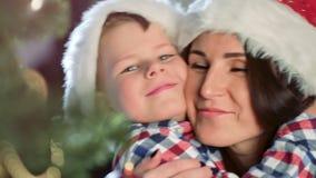 Szczęśliwa rodziny matka, śliczny mały syna przytulenie i ono uśmiecha się wpólnie blisko choinki w górę zbiory wideo