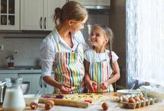 Szczęśliwa rodziny matka, córka i piec ugniatać ciasto w kuchni obraz royalty free