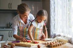 Szczęśliwa rodziny matka, córka i piec ugniatać ciasto w kuchni zdjęcia stock
