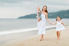 Szczęśliwa rodziny matka, dzieci na plaży morzem w lecie i Fotografia Royalty Free