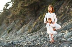 Szczęśliwa rodziny matka, dziecko robi joga i, medytujemy w lotosowym posi Zdjęcia Stock