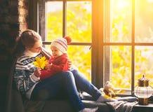 Szczęśliwa rodziny matka, dziecko w jesieni okno i Obrazy Stock