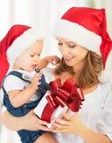 Szczęśliwa rodziny matka, dziecko z prezentem w Bożenarodzeniowych kapeluszach i Zdjęcia Royalty Free