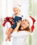 Szczęśliwa rodziny matka, dziecko z prezentem w Bożenarodzeniowych kapeluszach i Fotografia Stock