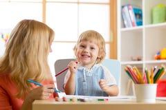 Szczęśliwa rodziny matka i dzieciaka syn wpólnie malujemy Kobieta pomaga dziecko chłopiec Fotografia Stock