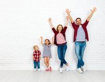 Szczęśliwa rodziny matka, ojciec, syn, córka na białej pustej ścianie Zdjęcia Stock