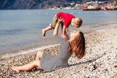 Szczęśliwa rodziny matka z dziecko synem siedzi morze plażą Zdjęcie Stock