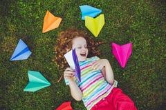 Szczęśliwa roześmiana dziewczyna rzuca papierowego samolot w zielonej trawie przy su zdjęcie stock