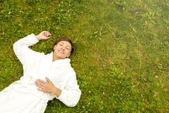 Szczęśliwa roześmiana kobieta kłama szerokie ręki w trawie zdjęcia royalty free
