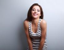Szczęśliwa roześmiana naturalna emoci młoda kobieta patrzeje na błękitnym backg Zdjęcia Stock
