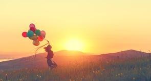 Szczęśliwa rozochocona dziewczyna biega przez łąkę przy sunse z balonami Zdjęcia Stock