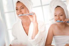 Szczęśliwa rozochocona matka i córka szczotkuje zęby wpólnie Obraz Stock