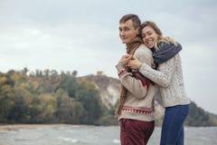 Szczęśliwa rozważna pary pozycja na rockowym plażowym pobliskim dennym huggin Fotografia Royalty Free