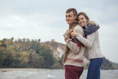 Szczęśliwa rozważna pary pozycja na rockowym plażowym pobliskim dennym huggin Zdjęcia Royalty Free