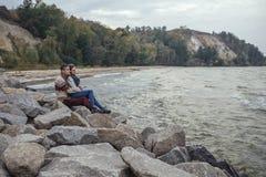 Szczęśliwa rozważna pary pozycja na rockowym plażowym pobliskim dennym huggin Fotografia Stock