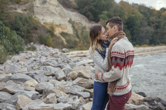 Szczęśliwa rozważna pary pozycja na rockowym plażowym pobliskim dennym huggin Obrazy Royalty Free