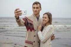 Szczęśliwa rozważna pary pozycja na rockowym plażowym pobliskim dennym huggin Zdjęcia Stock