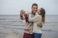Szczęśliwa rozważna pary pozycja na rockowym plażowym pobliskim dennym huggin Obraz Stock
