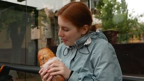 Szczęśliwa rudzielec dziewczyna cieszy się łasowania baguette zdjęcie wideo