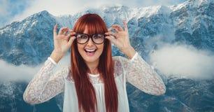 Szczęśliwa rudzielec kobieta jest ubranym eyeglasses przeciw snowcapped górom obrazy royalty free