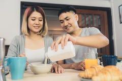 Szczęśliwa słodka Azjatycka para ma śniadanie i pije sok pomarańczowego po, zboże w mleku, chlebowy budził się w ranku zdjęcia stock