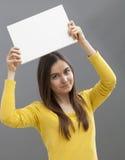 Szczęśliwa 20s dziewczyna robi reklamie w podnosić pustą wszywkę nad jej głowa Obrazy Royalty Free