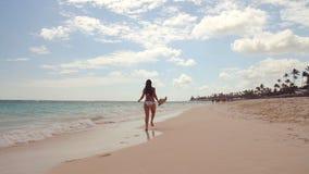 Szczęśliwa seksowna kobieta w bikini cieszy się tropikalnego morze i egzot wyrzucać na brzeg w Punta Cana, republika dominikańska zbiory